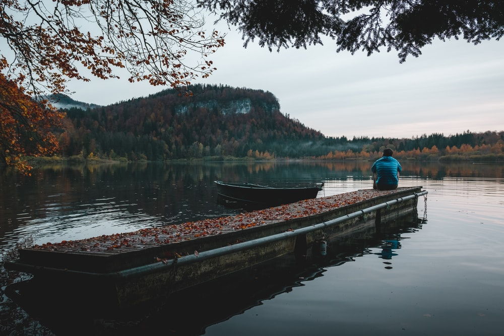 man in blue jacket sitting on brown wooden dock during daytime