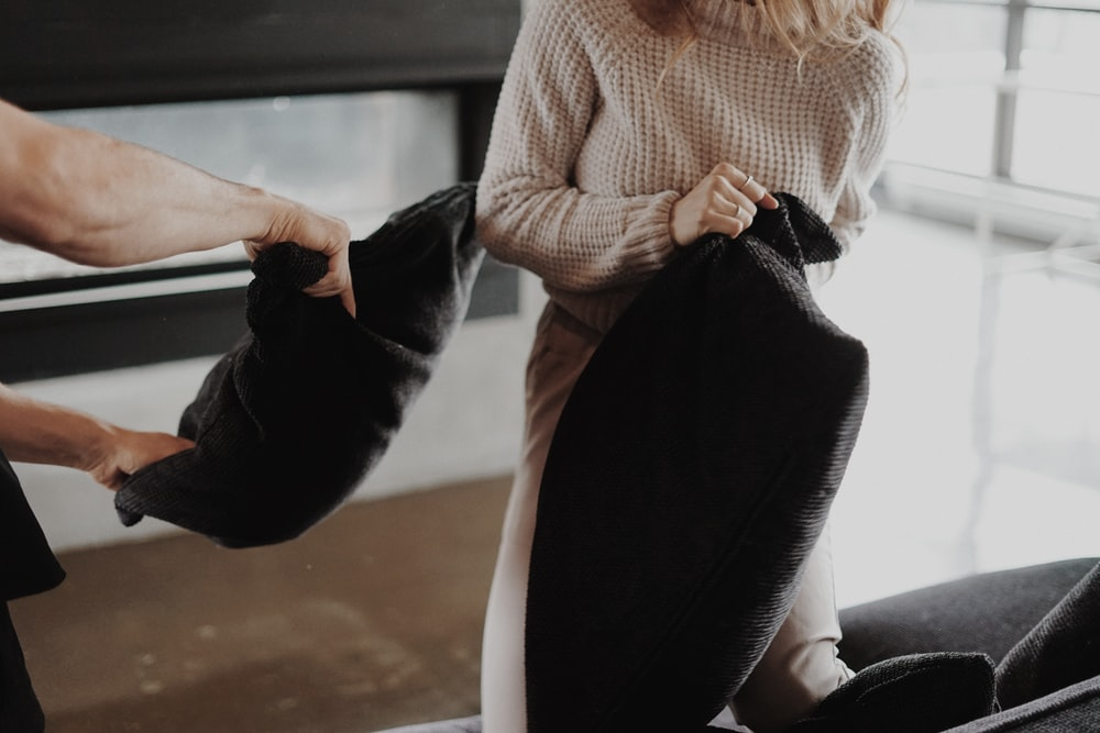 woman in white sweater and black pants sitting on white chair