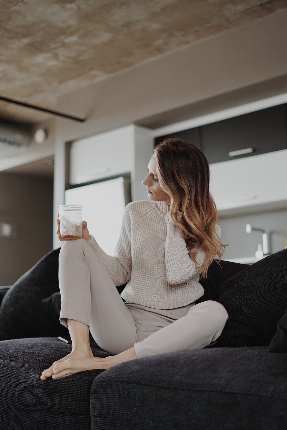 woman in white sweater sitting on black couch