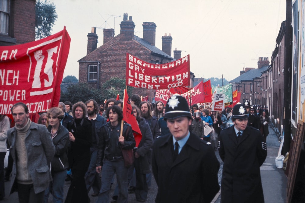 people in black suit standing near red and white flag during daytime