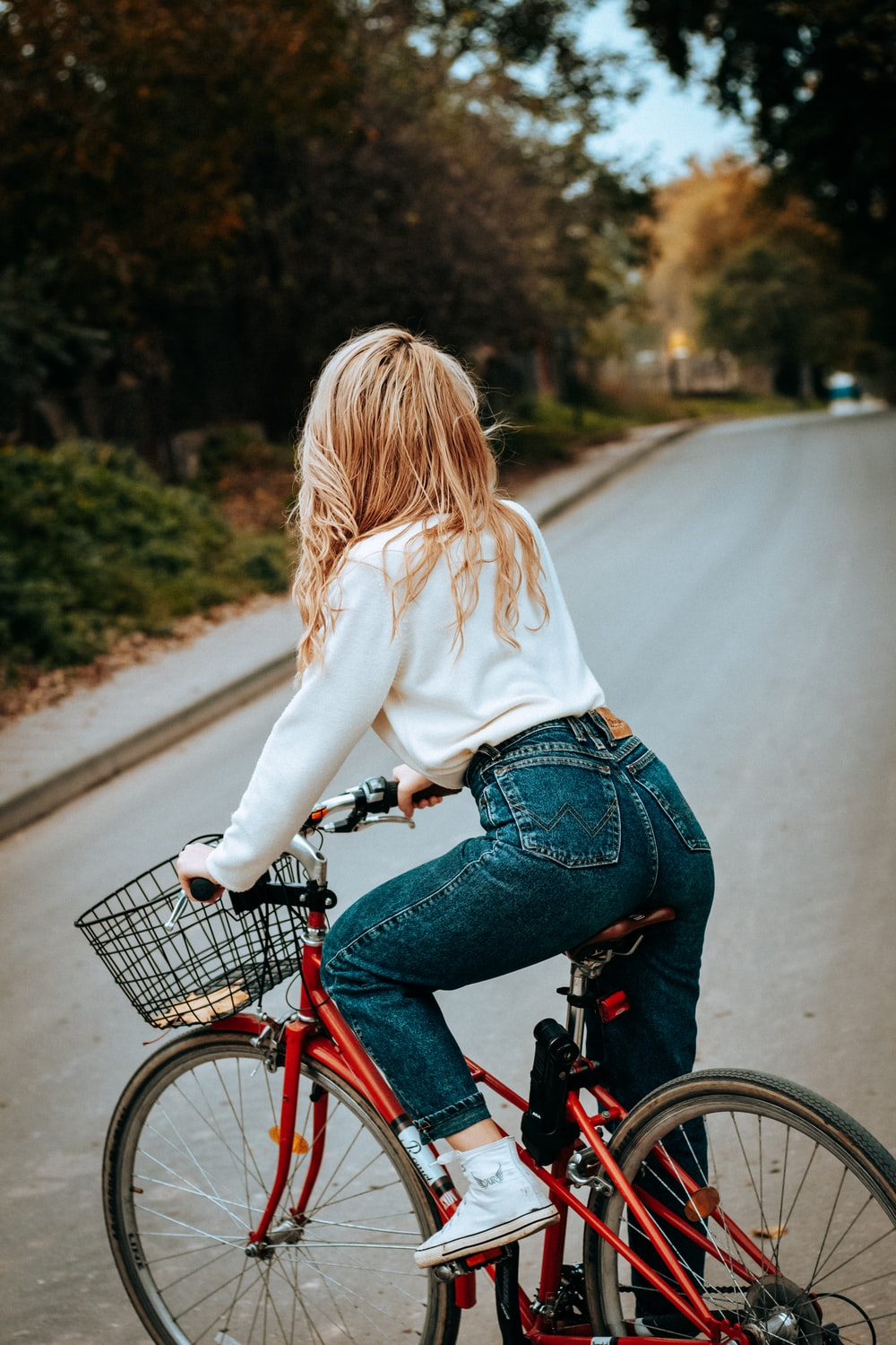 woman in white sweater and blue denim jeans riding on red bicycle on road during daytime