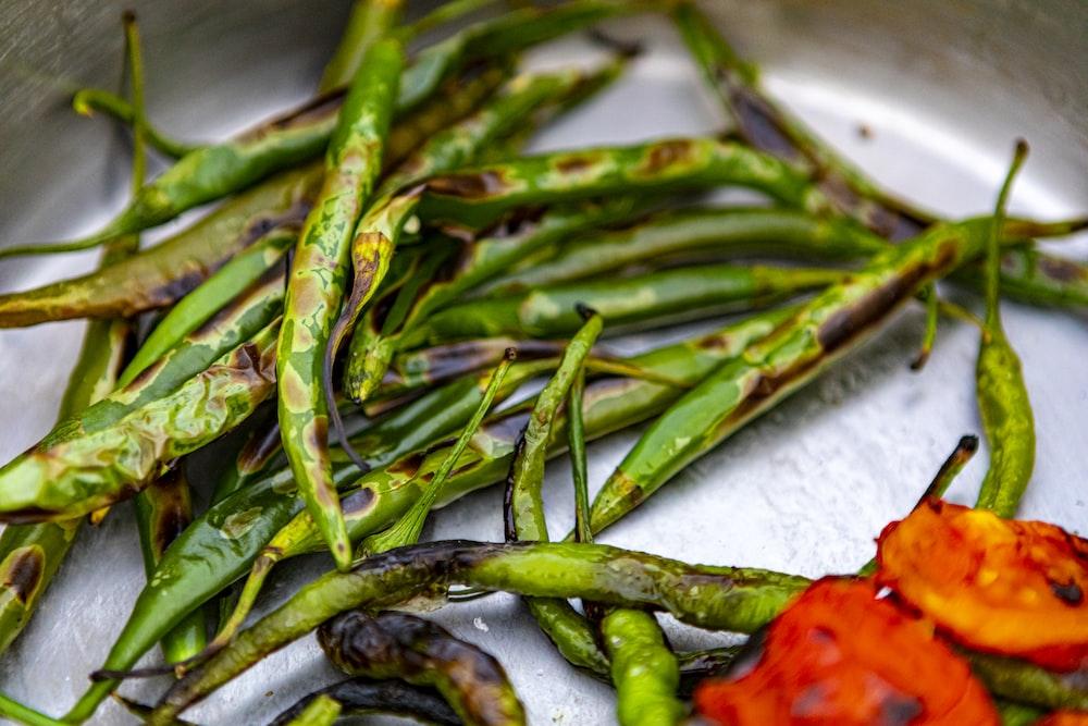 green chili on white textile
