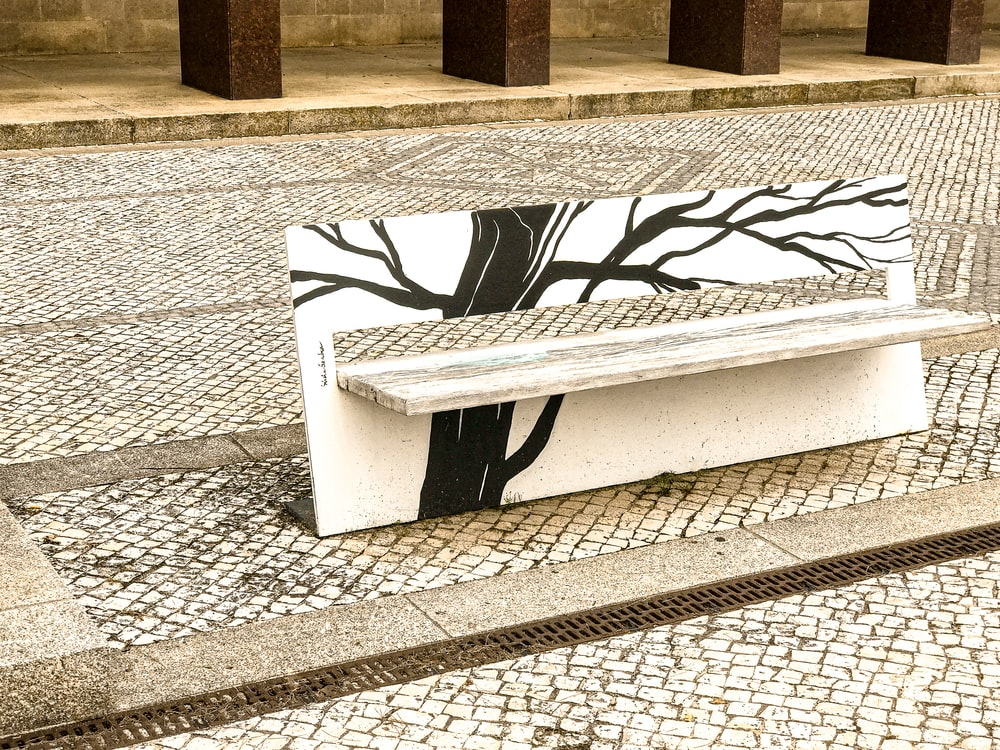 white and black bench on gray concrete floor
