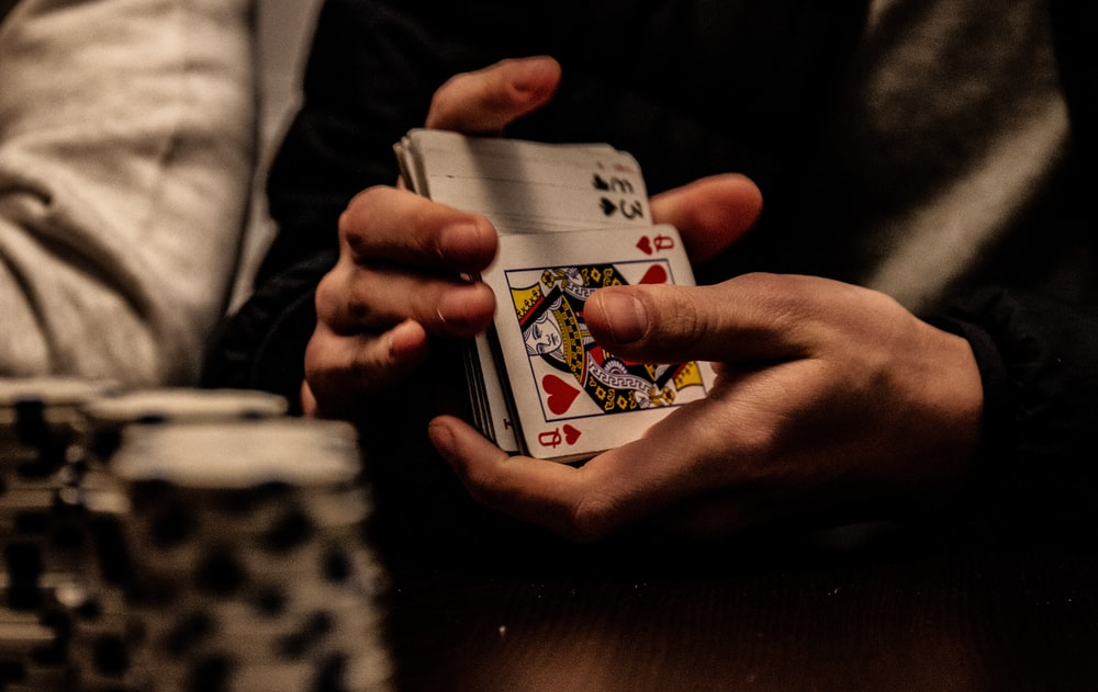 person holding king of spade playing card