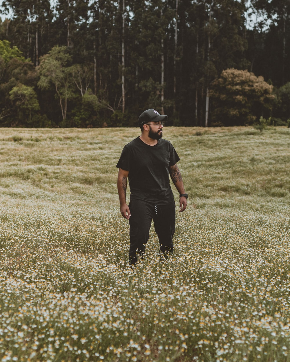 man in black crew neck t-shirt and black pants standing on green grass field during