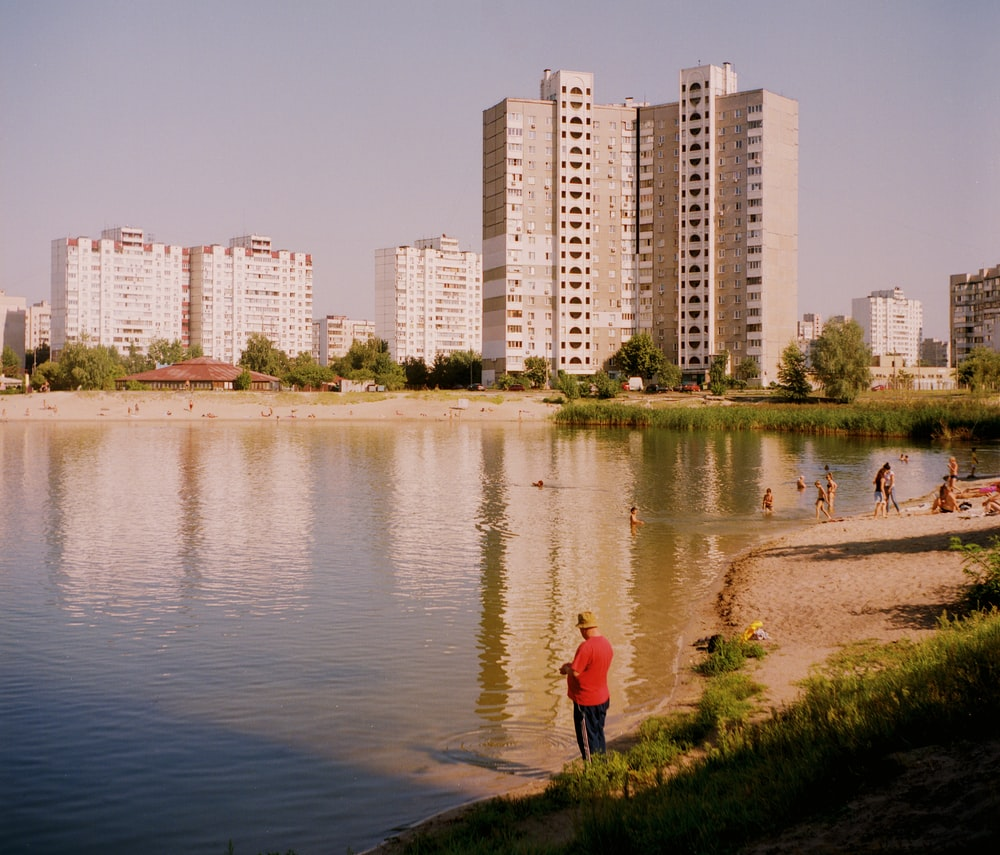woman in red jacket walking on green grass near body of water during daytime