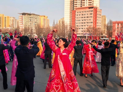 people in red and blue dress dancing on street during daytime north korea zoom background