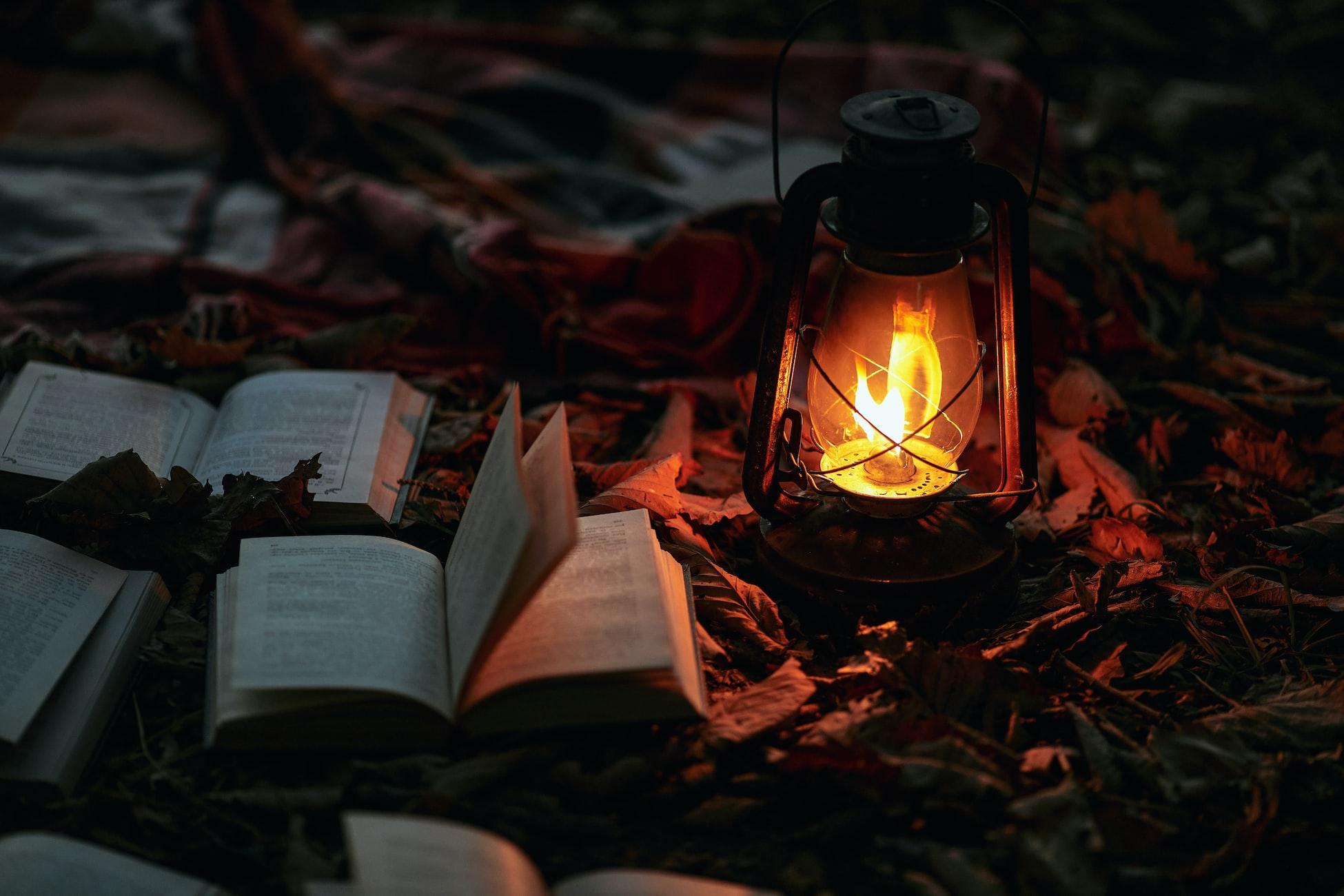 Горящая керосиновая лампа и открытые книги