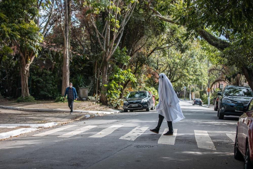 man in white thobe walking on the street during daytime