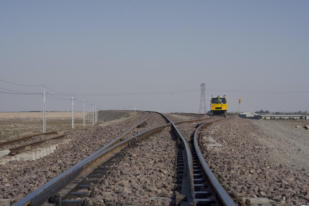 yellow and black train on rail tracks under gray sky