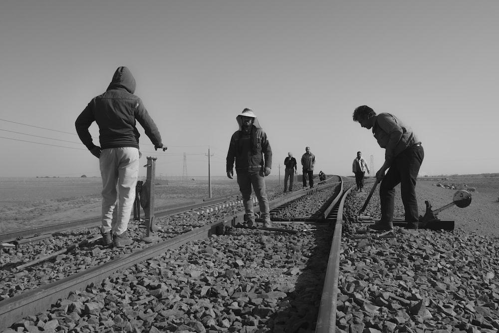 grayscale photo of people walking on train rail