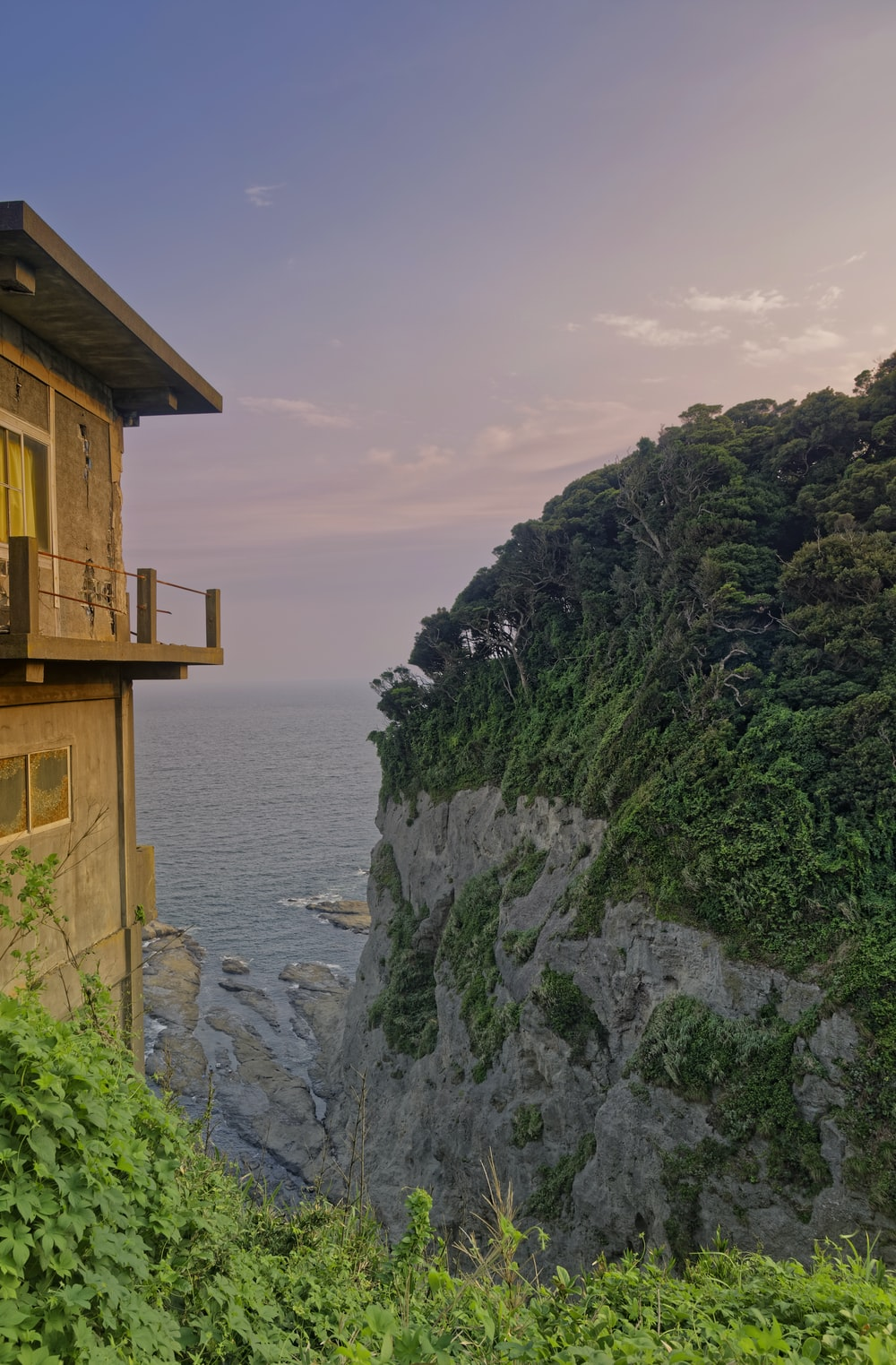 brown wooden house on cliff by the sea during daytime