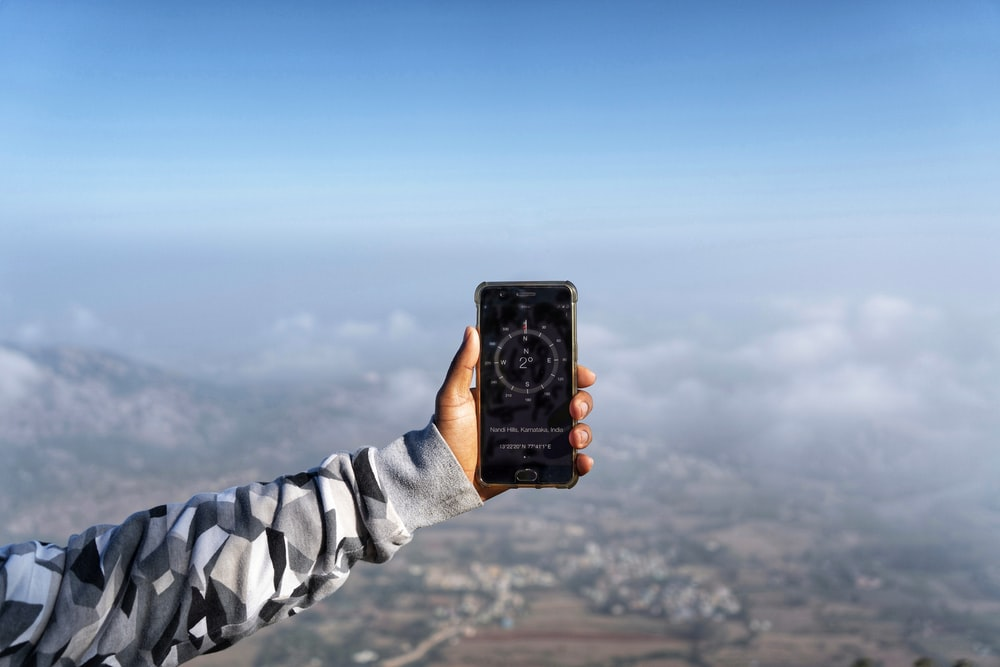 person holding black smartphone taking photo of blue sky during daytime