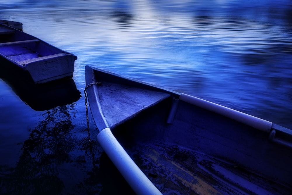 blue boat on body of water during daytime