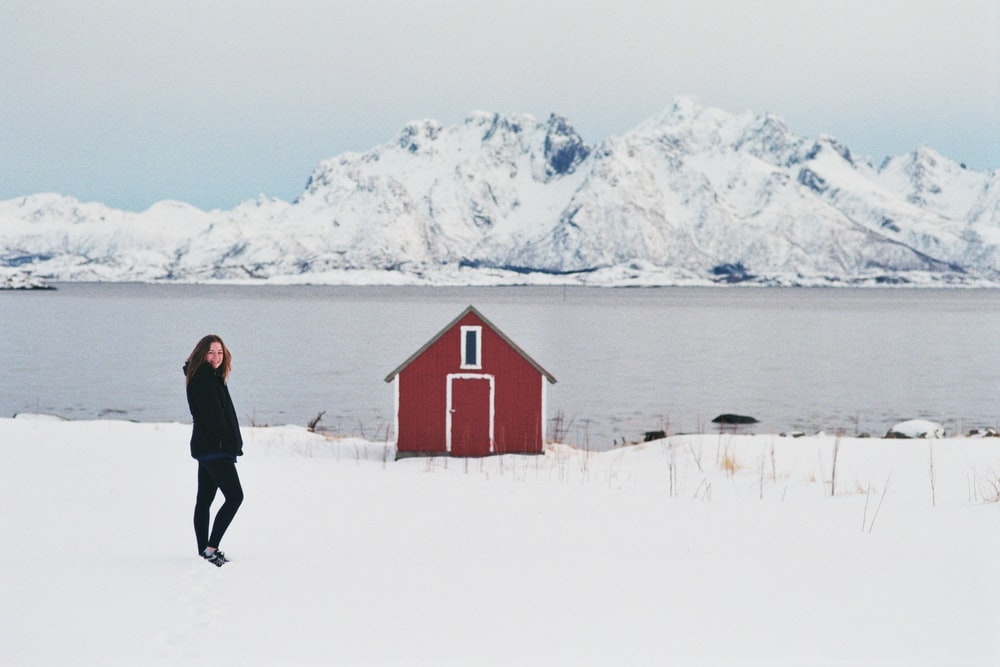 man in black jacket and black pants standing on snow covered ground near red house during