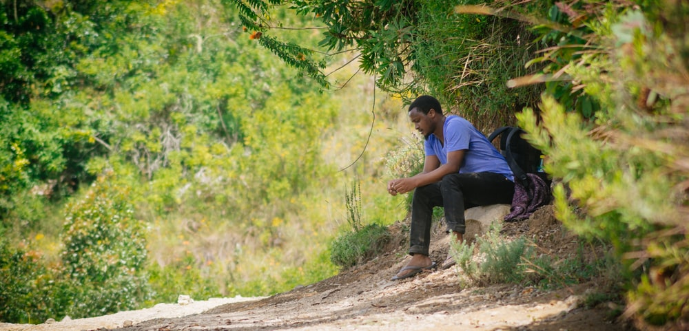 man in blue t-shirt and black pants sitting on brown tree trunk during daytime