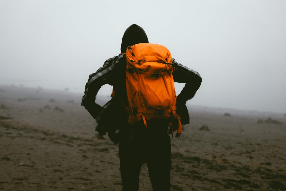 man in orange and black jacket and black pants standing on brown sand during daytime
