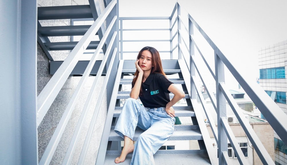 woman in black crew neck t-shirt and gray pants sitting on white wooden staircase