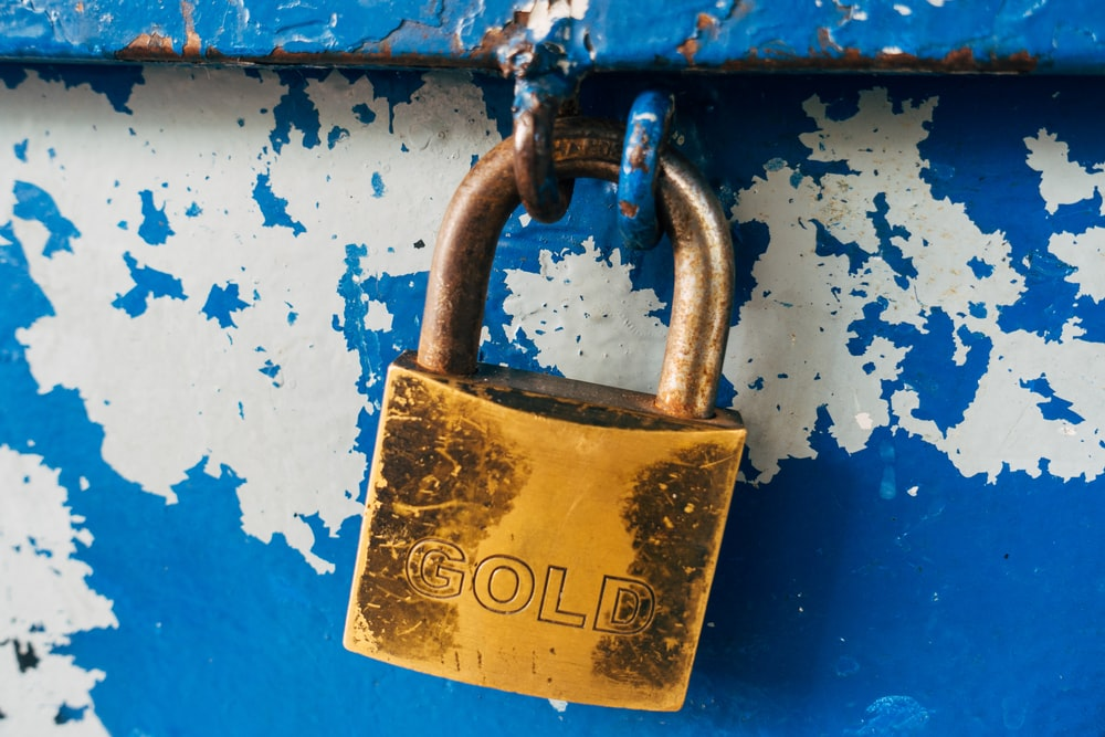 gold padlock on blue and white floral door