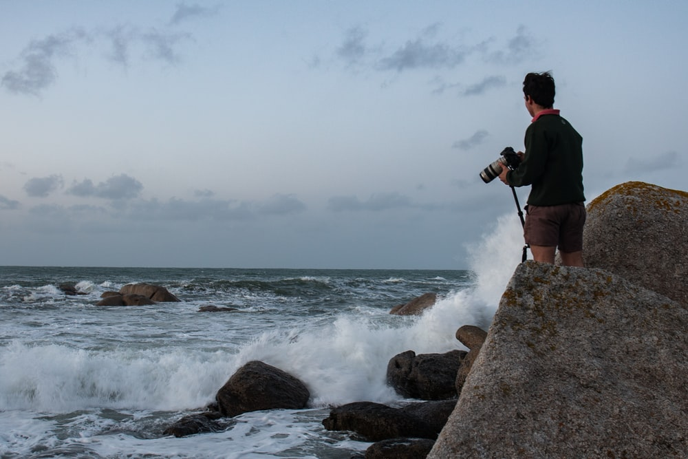 man in black jacket and black pants standing on rocky shore during daytime