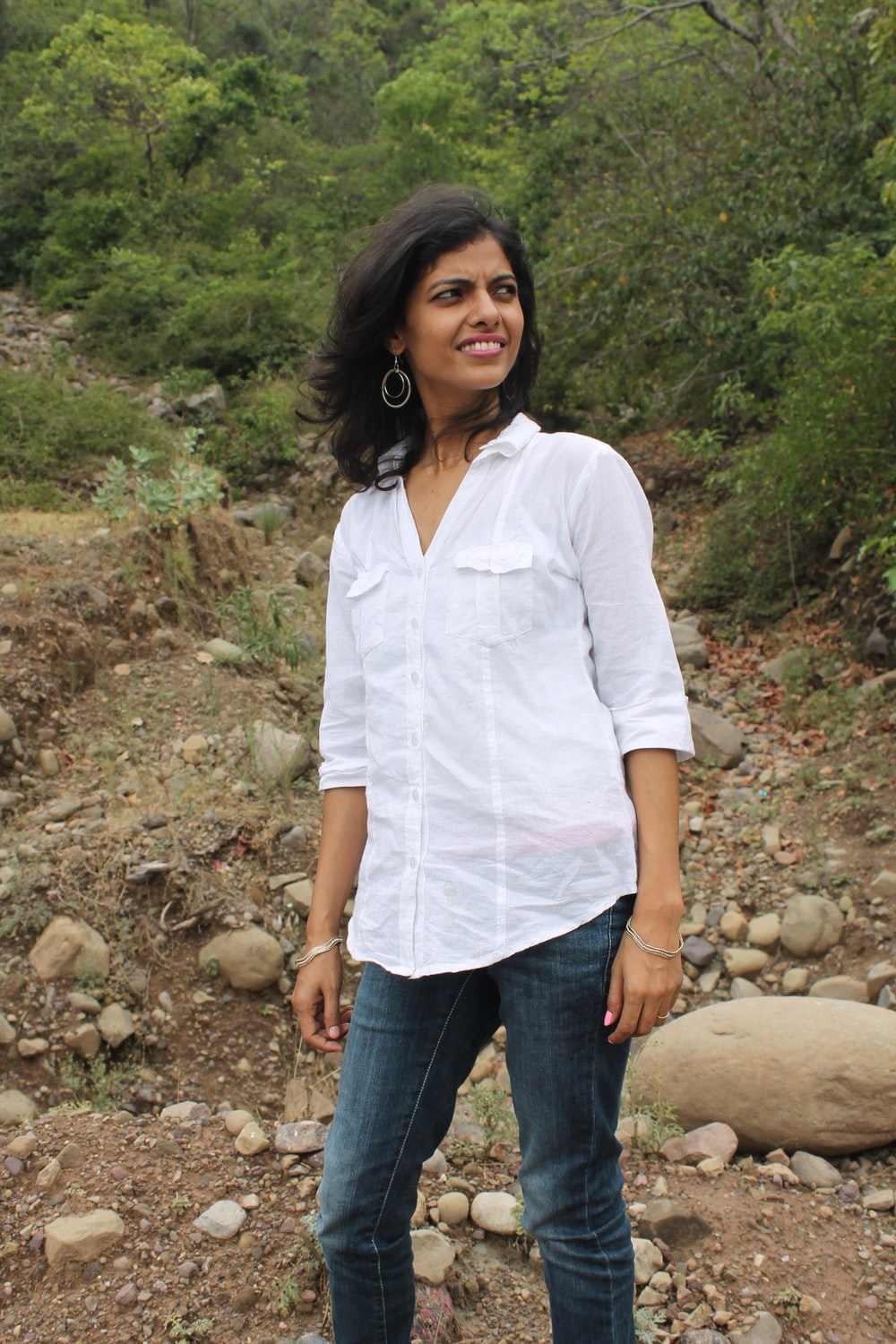 woman in white button up shirt and blue denim jeans standing on rocky ground during daytime