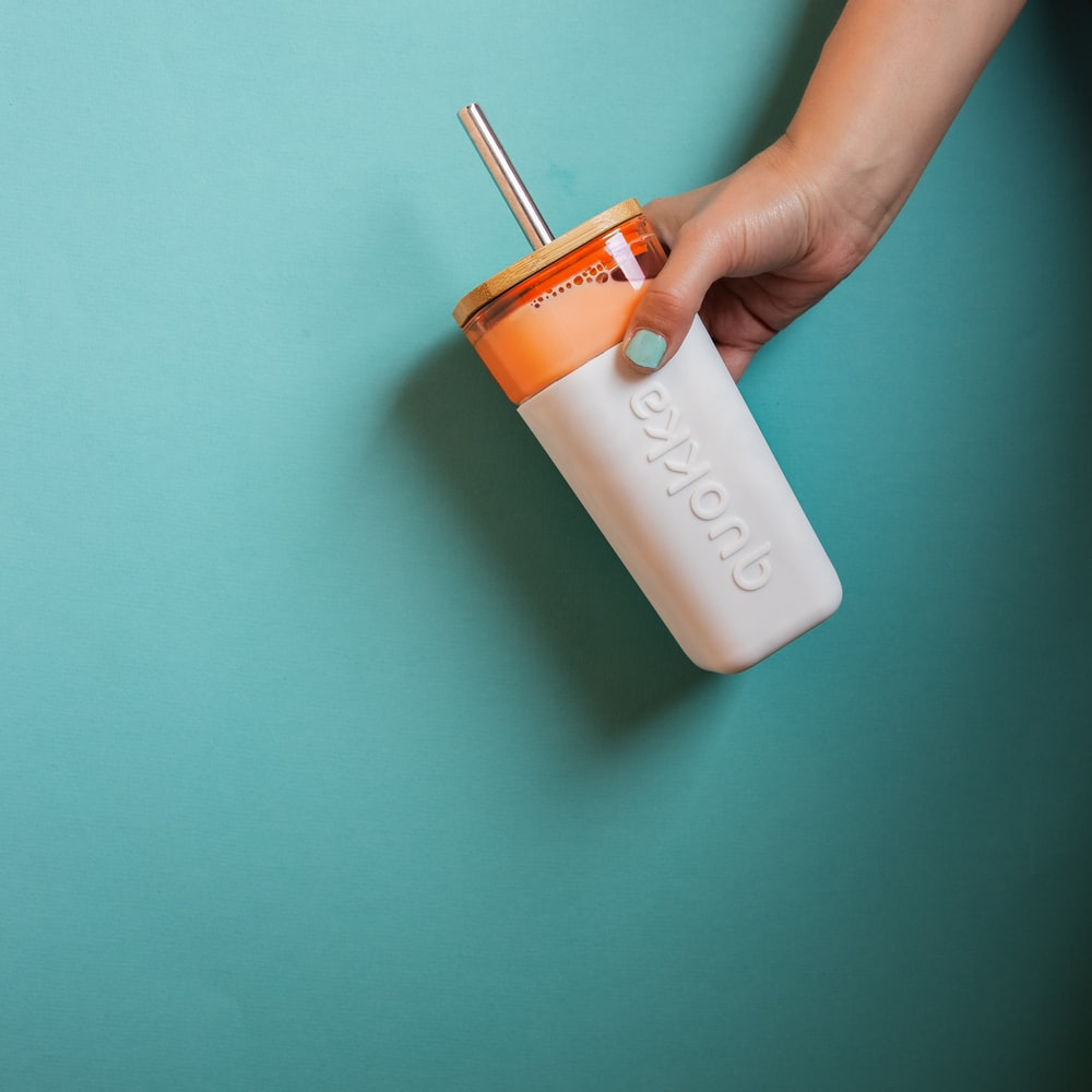 person holding white and orange plastic bottle