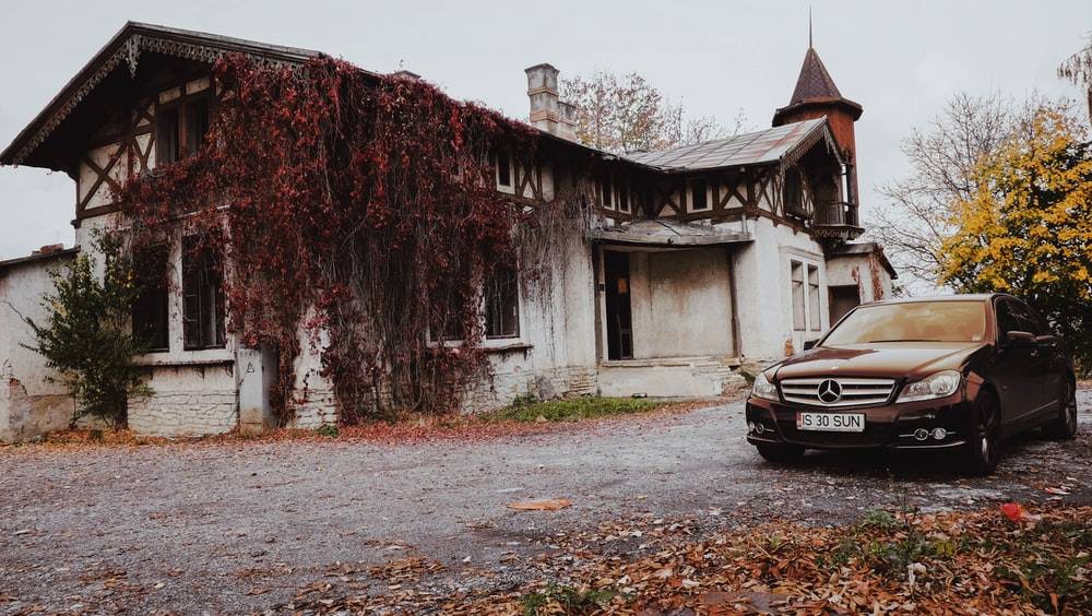 black car parked beside brown wooden building during daytime