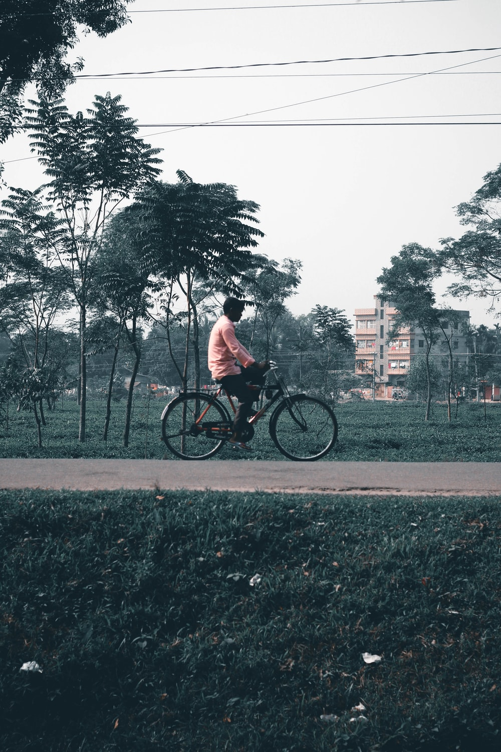 man in white t-shirt riding bicycle on road during daytime