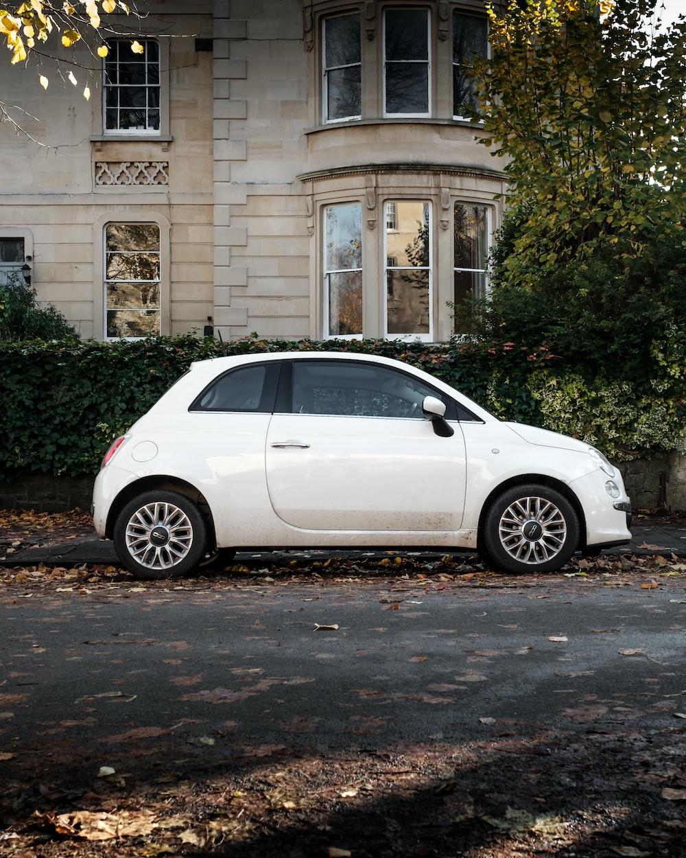 white 5 door hatchback parked beside brown concrete building during daytime