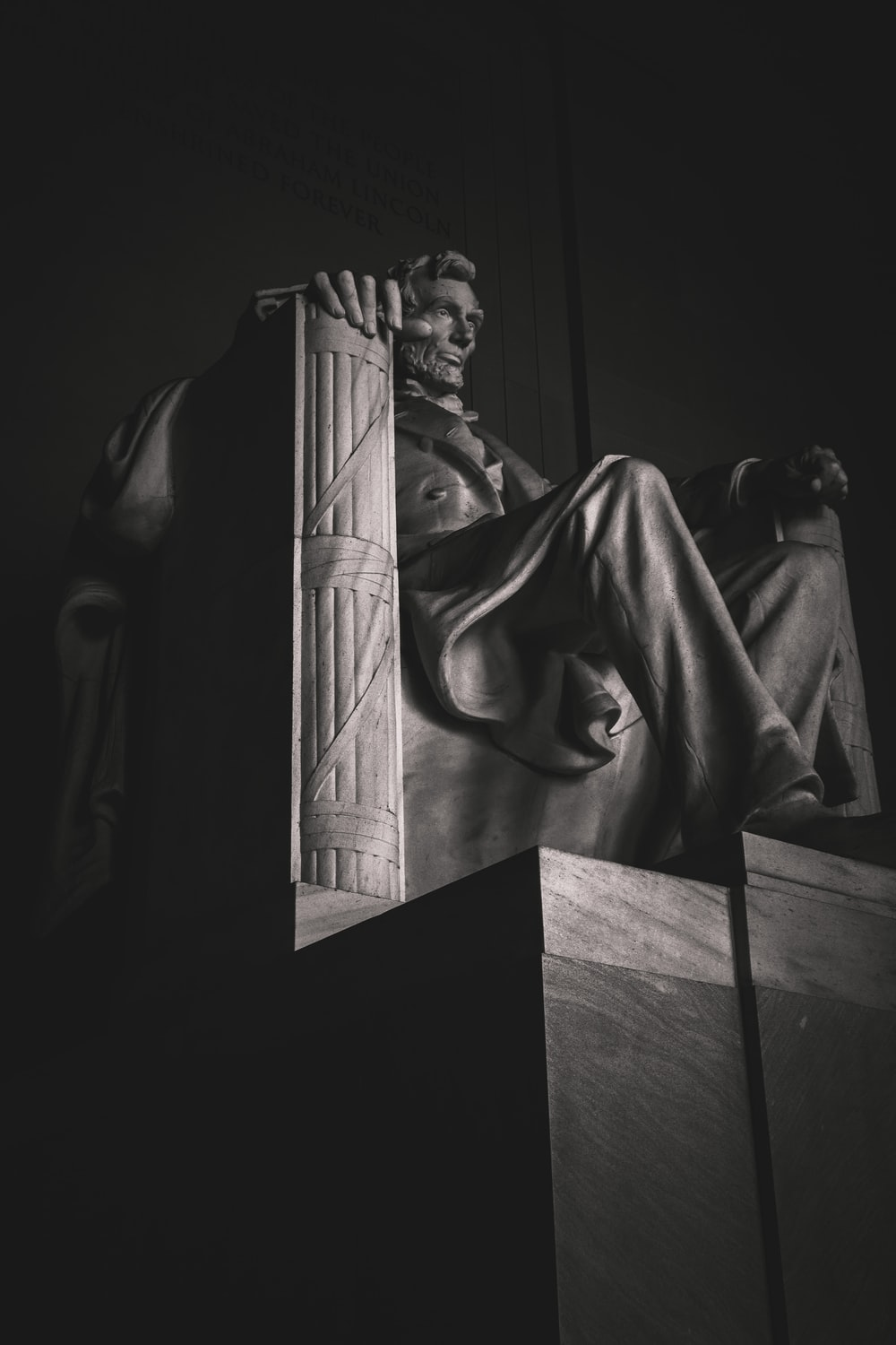man in robe statue in grayscale photography