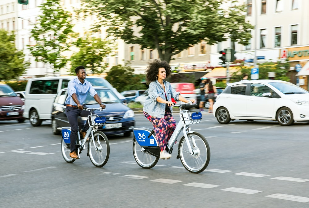man and woman riding bicycle on road during daytime