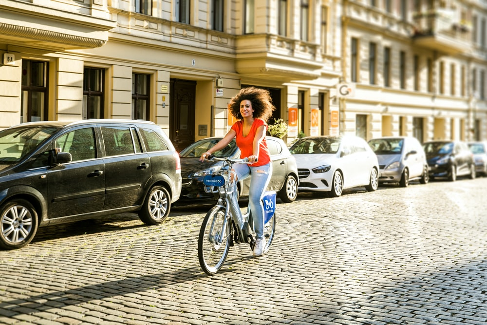 woman in white long sleeve shirt riding on bicycle during daytime