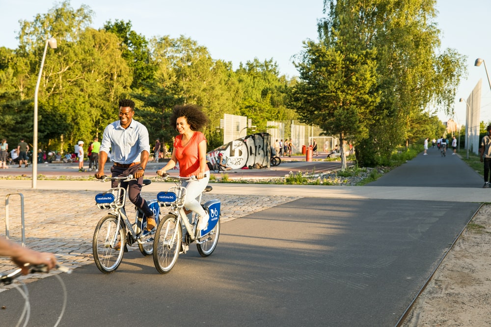 man and woman riding on bicycle on road during daytime