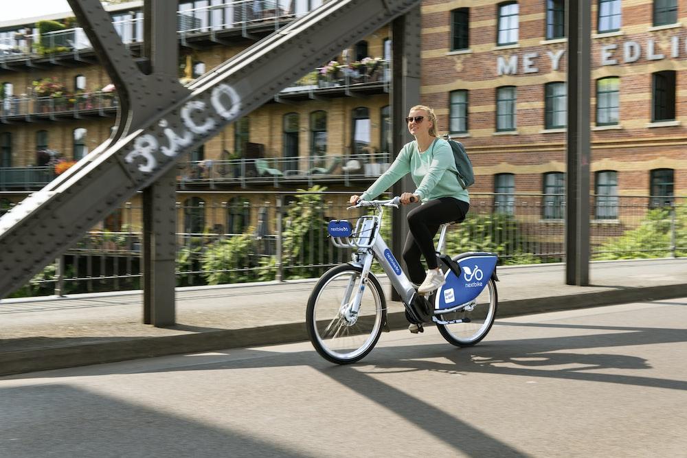 man in green jacket riding on bicycle during daytime