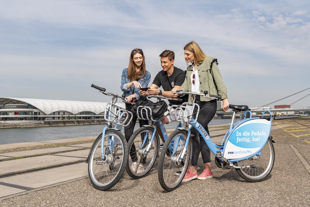 3 women riding on blue and black bicycle during daytime