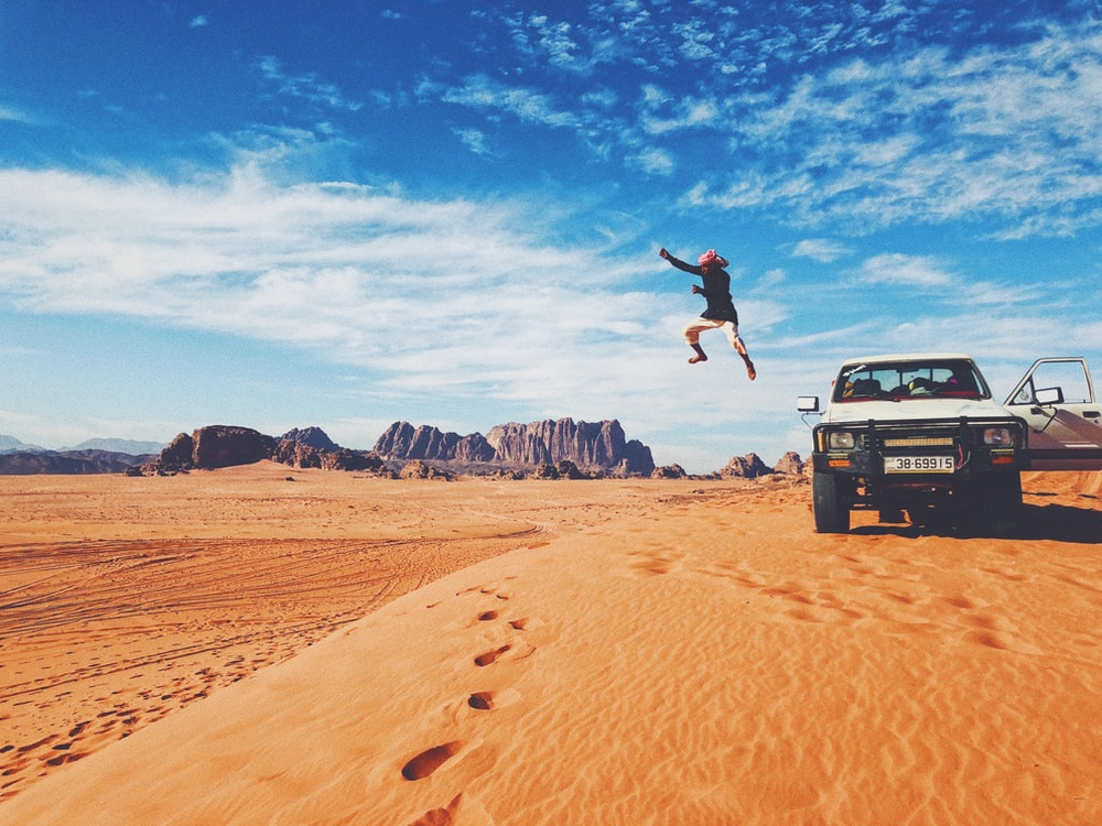 man jumping on brown sand under blue sky during daytime