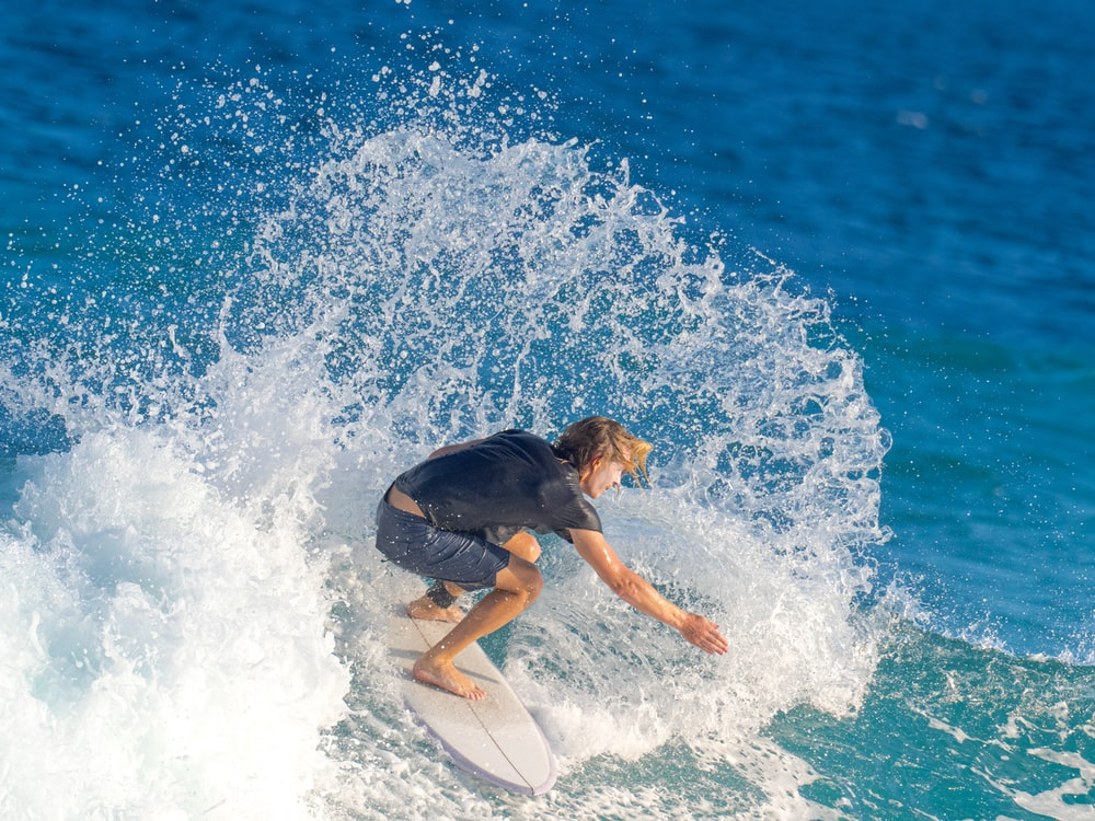 man in black shorts surfing on blue sea during daytime