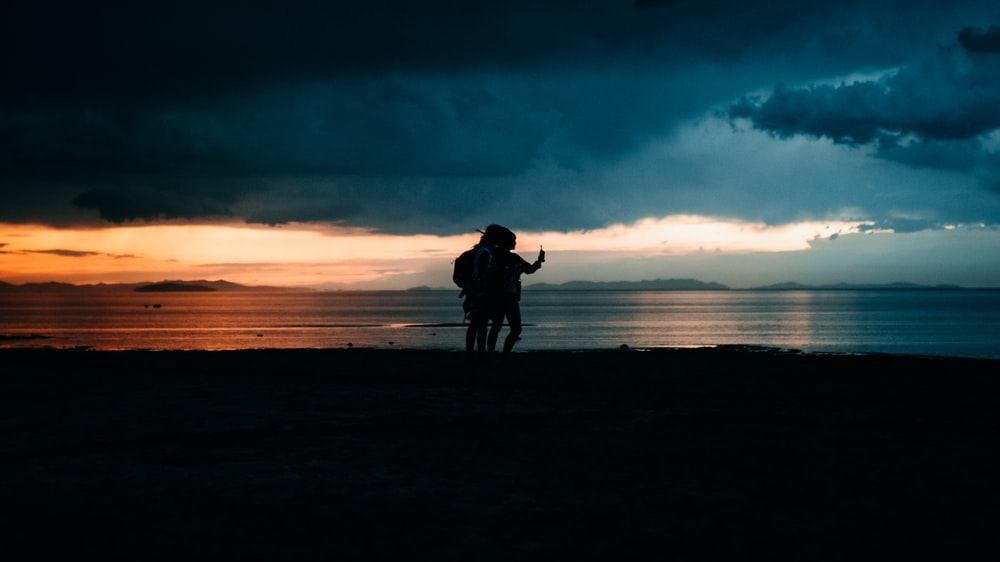 silhouette of man and woman walking on beach during sunset