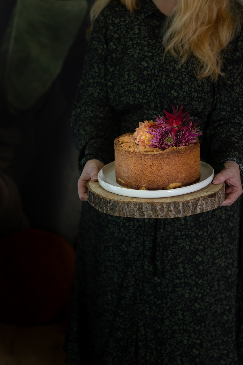 woman holding brown and white cake