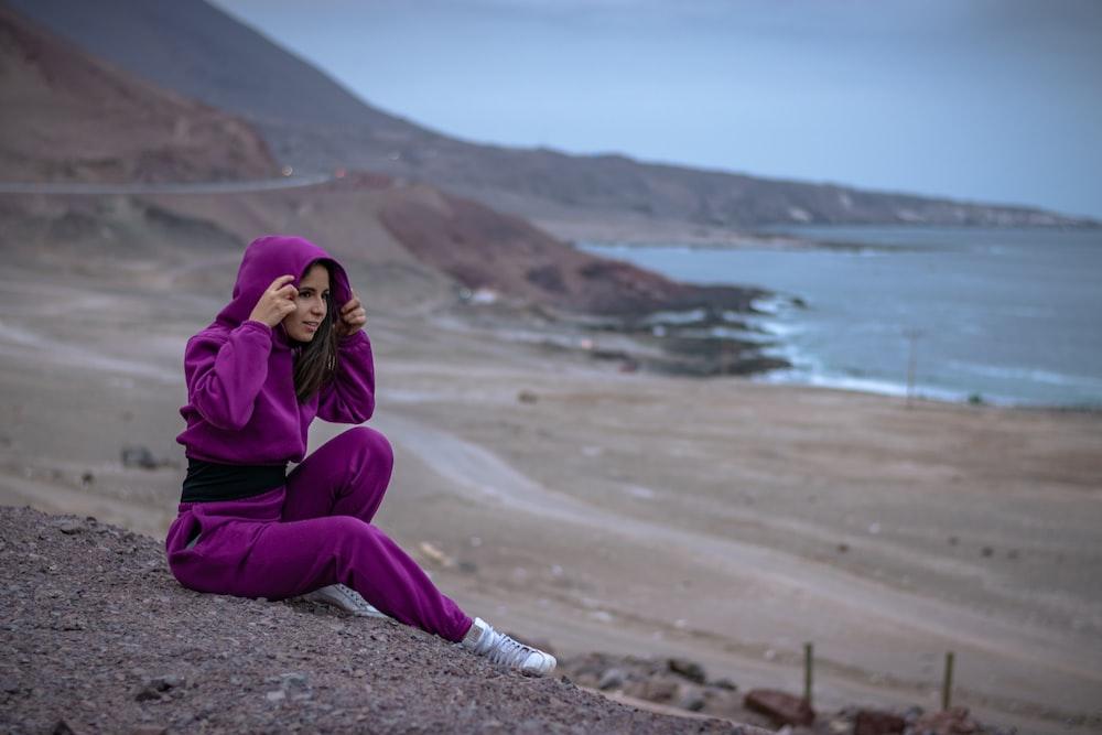 woman in purple hijab and purple long sleeve dress sitting on brown sand near body of near near near near