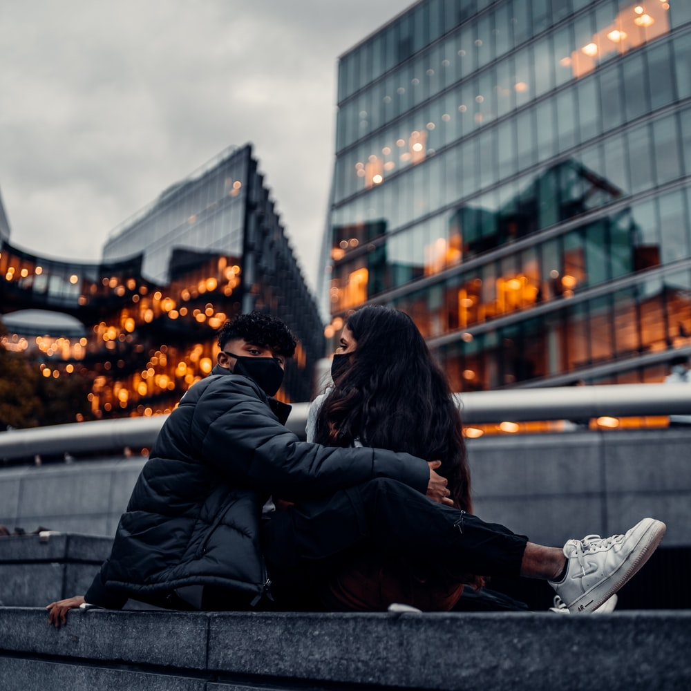 man and woman sitting on gray concrete bench during daytime