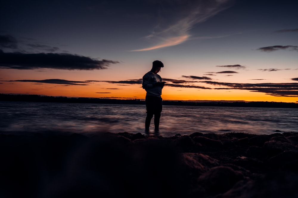 silhouette of woman standing on rocky shore during sunset