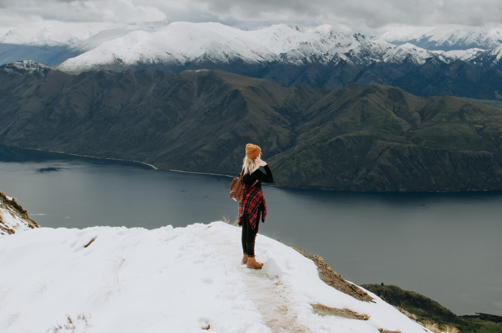 woman in black jacket and brown pants standing on snow covered ground near lake during daytime