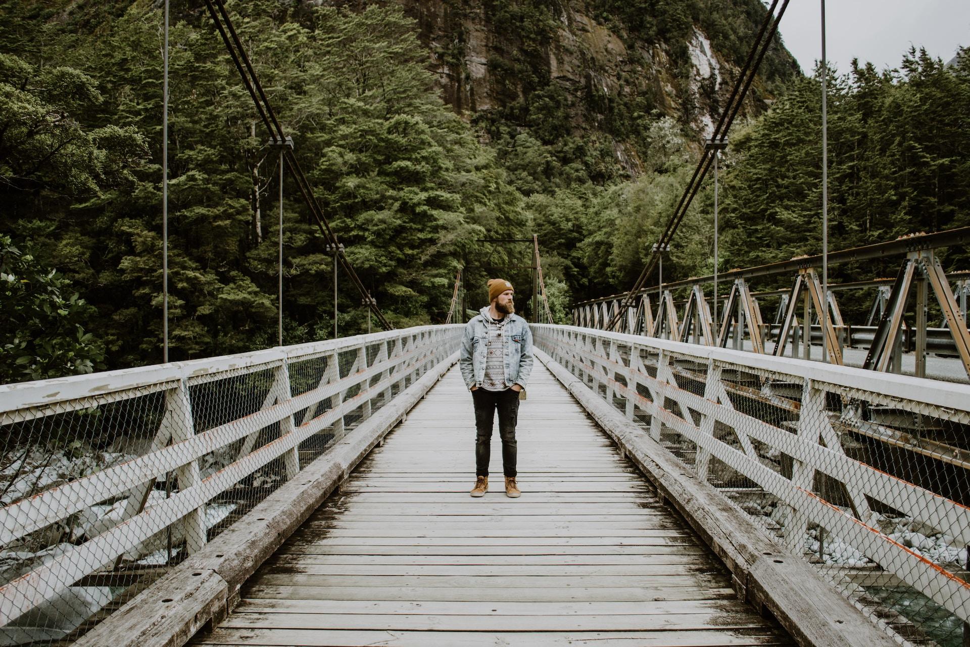 woman in black jacket and blue denim jeans walking on wooden bridge