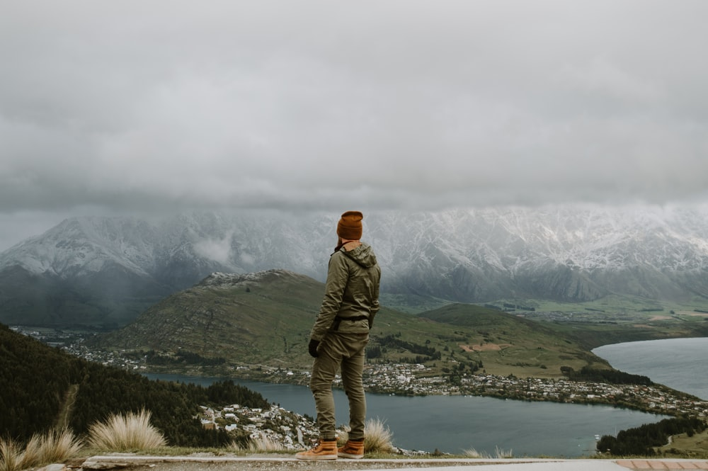 man in green jacket standing on rock near body of water during daytime