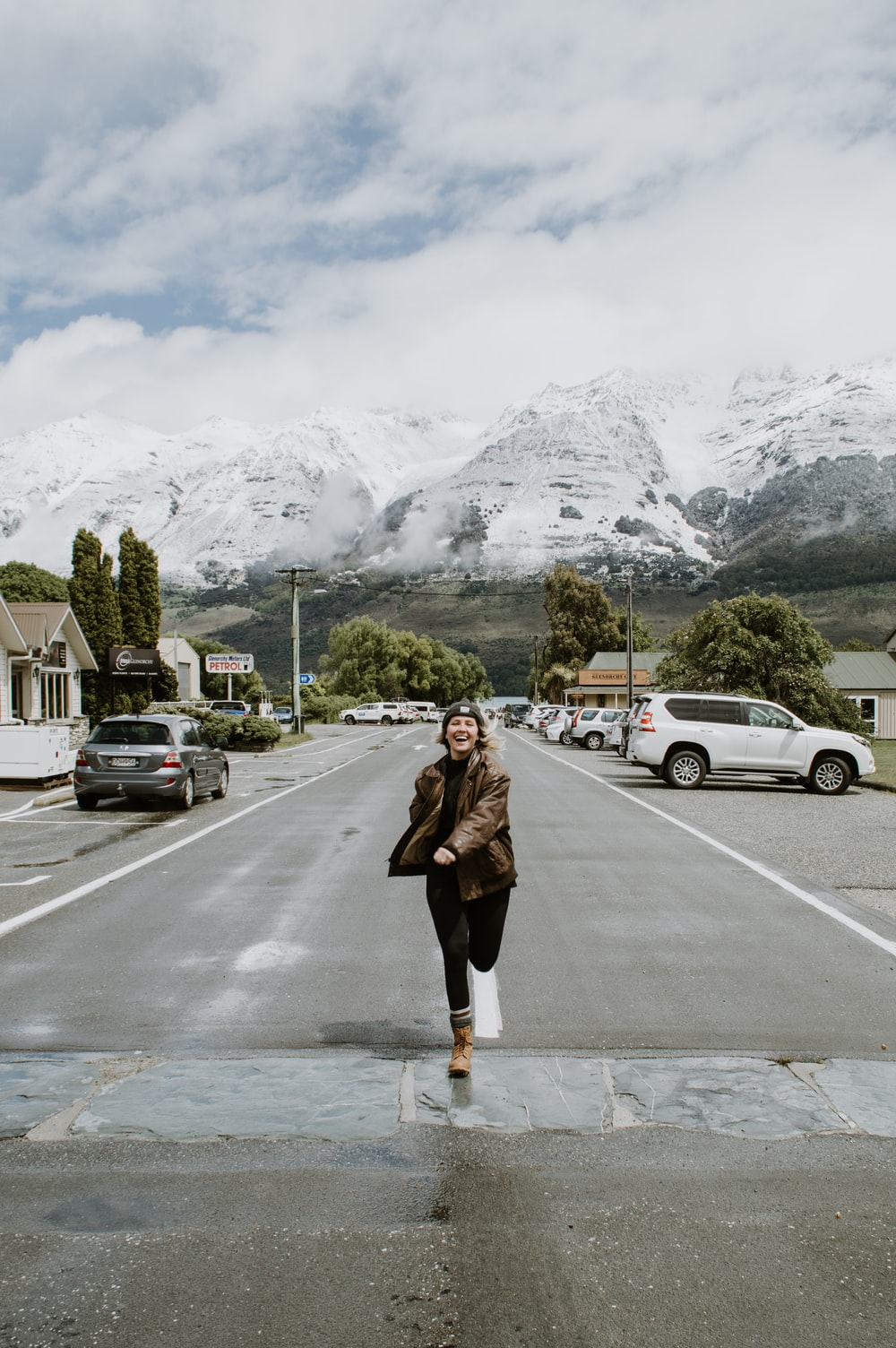 woman in brown coat standing on road near mountain range during daytime
