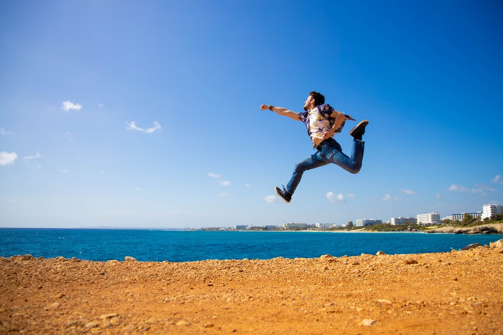 man in black shirt jumping on brown sand near body of water during daytime