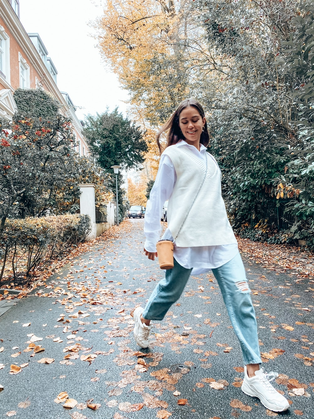 woman in white coat standing on brown leaves during daytime
