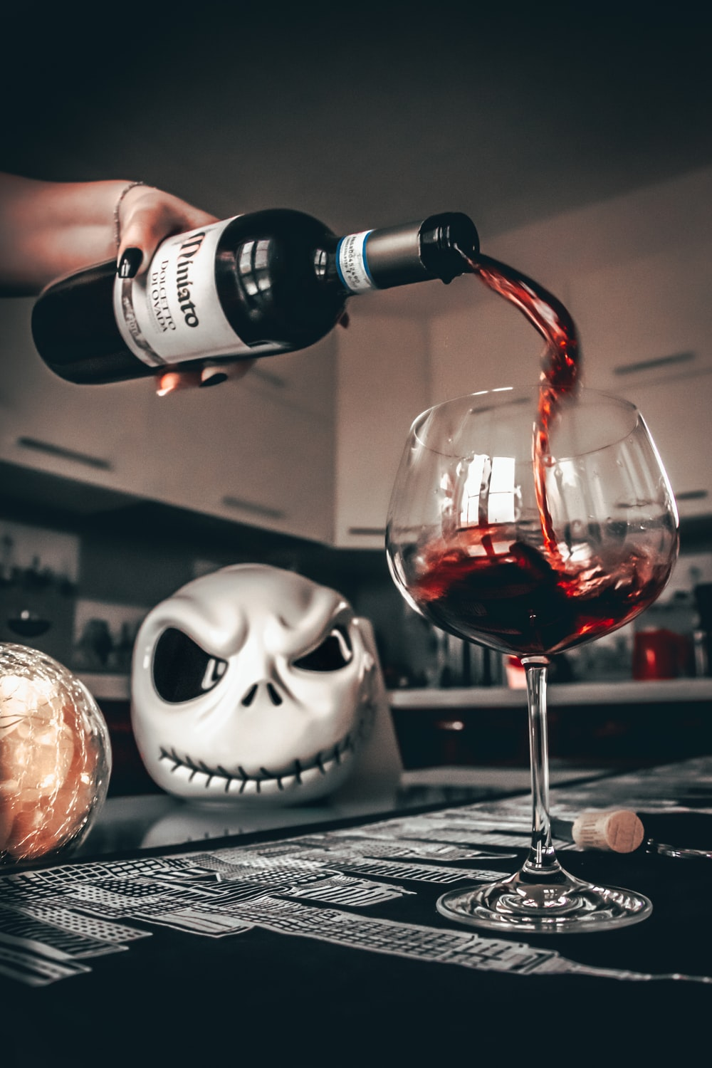 white and black skull with wine glass on table