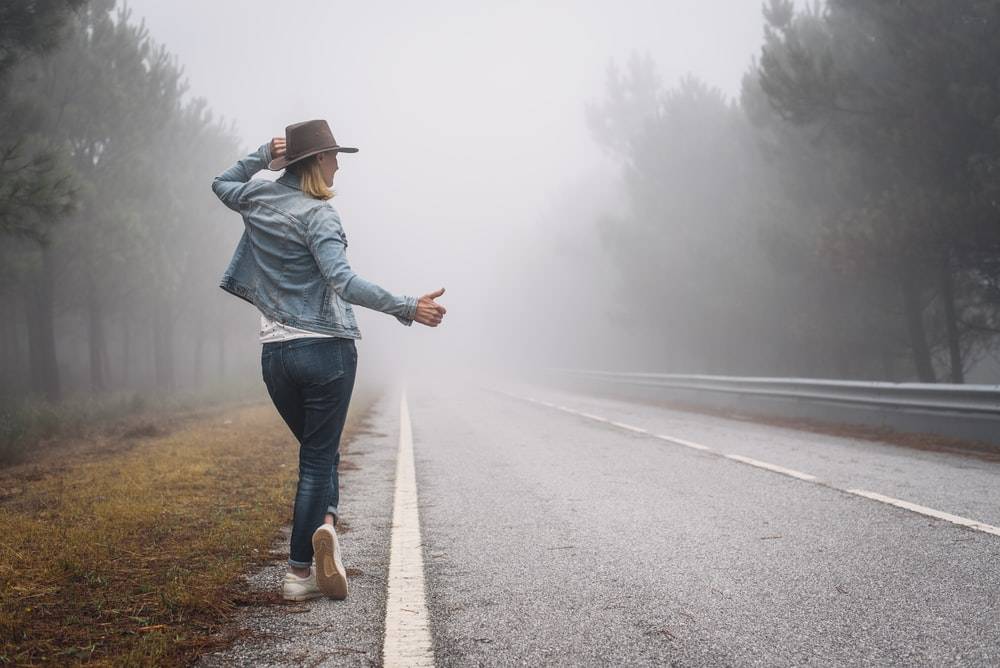 woman in blue denim jacket and blue denim jeans walking on road during daytime
